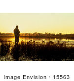 #15563 Picture Of A Duck Hunter Standing In Reeds Against An Orange Sunrise