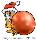 #22975 Clip Art Graphic Of A Cardboard Shipping Box Cartoon Character Wearing A Santa Hat Standing With A Christmas Bauble