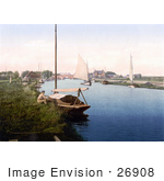 #26908 Stock Photography Of A Man Sitting By A Boat On The River Thurne Near The Medieval Bridge In Potter Heigham Norfolk East Anglia England