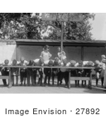 #27892 Historical Stock Photo Of An Excited Boy Clinging To A Basketball Hoop Pole While He And A Teacher Watch Boys Shoving Their Faces Into Pies While Competing During A Pie Eating Contest In 1923