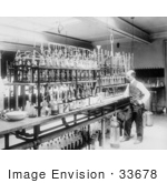 #33678 Stock Photo Of A Man A Chemical Laborator Standing At A Counter In Front Of A Line Of Bottles Testing Whiskey