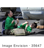 #35647 Stock Photo Of Male And Female US Navy Sailors Removing A Data Bus From The Nose Of A Hh-60h Seahawk