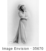 #35670 Stock Photo Of A Beautiful Woman, Broadway Actress Julia Marlowe, Standing, Wearing A Hat And Dress And Touching Her Face While Looking Off To The Right by JVPD