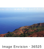 #36525 Stock Photo Of Red Na Pali Coast Cliffs Looking Over Rippling Blue Waters Of The Pacific Oceanm With Clouds In The Distance