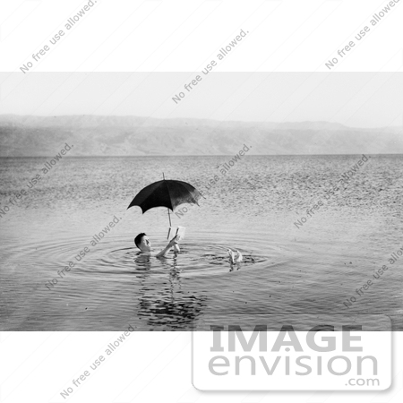 #12872 Picture of a Man Floating With Umbrella and Book in the Dead Sea by JVPD