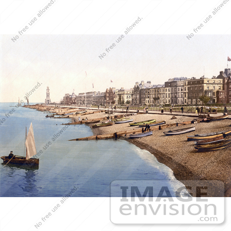 #26847 Stock Photography of a Man Rowing a Boat Near a Beach With Boats Lined up on the Shore and Waterfront Buildings in Herne Bay Kent South East England by JVPD