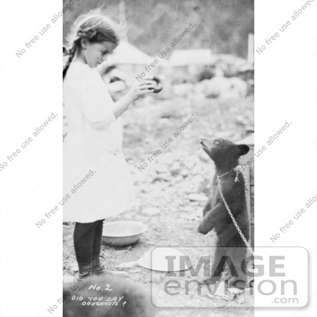 #27890 Historical Stock Photo of a Litte Girl Holding Up A Donut To A Hungry Bear Cub That Is Standing On Its Hind Legs And Tied By A Chain by JVPD