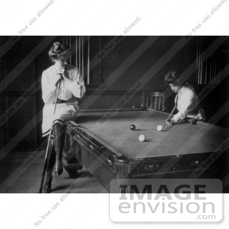 #30201 Historical Black and White Stock Photo of a Woman Leaning On A Cue Stick And Sitting On The Edge Of A Pool Table While Watching Her Friend Play Billiards In 1903 by JVPD
