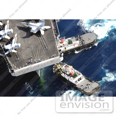 #30728 Stock Photo of Tugboats Beside An Aircraft Carrier With Military Jets On Board In Guam by JVPD