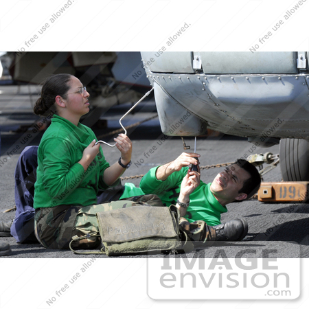 #35647 Stock Photo Of Male And Female U.S. Navy Sailors Removing A Data Bus From The Nose Of A HH-60H Seahawk by JVPD
