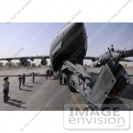 #35648 Stock Photo Of U.S. Airmen Watching A Hh-60 Pave Hawk Helicopter Loading Into A C-17 Globemaster Iii Aircraft On Joint Base Balad, Iraq by JVPD