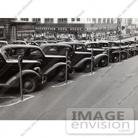 #37681 Stock Photo Of Vintage Cars Lined Up In Parking Spots With Parking Meters On The Sidewalk In Omaha, Nebraska, 1938 by JVPD
