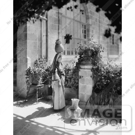 #43469 RF Stock Photo Of A Black And White Ramallah Woman Balancing A Jug On Her Head On A Patio by JVPD