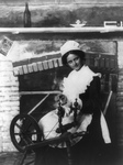 Free Picture of Woman Using a Spinning Wheel by a Fireplace