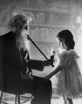 Free Picture of Little Girl Lighting an Old Man's Pipe
