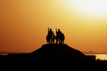 Free Picture of Soldiers and Children Silhouetted Against a Sunset