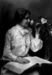 Free Picture of Helen Keller Smelling a Rose and Reading Braille