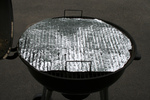Foil With Holes Covering a Rusty BBQ Grill