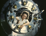 Photo of a Riveter Woman Framed by a Circular Opening of a Cowling, Working on Lower Section