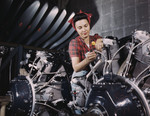 Woman standing between sections of motor, working with wires