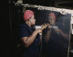 Photo of an African American Riveter Woman Drilling on the Side of a Bomber