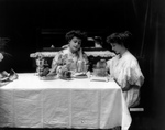 Two Women Using a Toaster at a Table