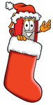 Clip Art Graphic of a Book Cartoon Character Wearing a Santa Hat Inside a Red Christmas Stocking
