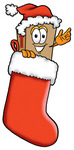 Clip Art Graphic of a Cardboard Shipping Box Cartoon Character Wearing a Santa Hat Inside a Red Christmas Stocking