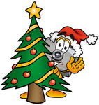 Clip Art Graphic of a Flash Camera Cartoon Character Waving and Standing by a Decorated Christmas Tree