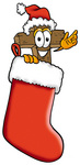 Clip Art Graphic of a Wooden Cross Cartoon Character Wearing a Santa Hat Inside a Red Christmas Stocking