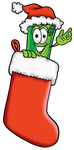 Clip Art Graphic of a Rolled Greenback Dollar Bill Banknote Cartoon Character Wearing a Santa Hat Inside a Red Christmas Stocking