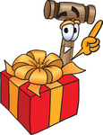 Clip Art Graphic of a Wooden Mallet Cartoon Character Standing by a Christmas Present