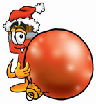 Clip Art Graphic of a Red Paintbrush With Yellow Paint Cartoon Character Wearing a Santa Hat, Standing With a Christmas Bauble