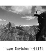 #41171 Stock Photo Of A Lone Man Standing On An Overhanging Rock Cliff At Glacier Point With A View Of Half Dome And The Valley Of Yosemite National Park California