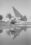 Man on Camel Near Pool of Water, Pyramids in the Background