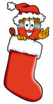 Clip Art Graphic of a Red Paintbrush With Yellow Paint Cartoon Character Wearing a Santa Hat Inside a Red Christmas Stocking